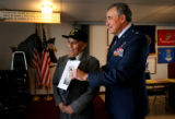 (PG078) Gen. Sal Villano holds up an old photo while joking with World War II veteran Richard...