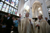 At his ordination, Bishop James Conley blesses the crowd with Archbishop Charles Chaput at...