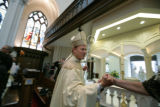 Bishop James Conley is congratulated as he leaves the Cathedral Basilica of the Immaculate...