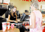 Jill Skinner waits for change from barista Brooke Skinner while buying coffee at Dazbog Coffee...