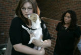 Andrea Gliva holds her sister's dog Lage, who was saved from the house fire after the Dick family...