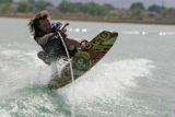 Dave Johnson jumps the wake of the boat pulling him while wakeboarding around Boyd Lake near...