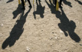 Shadows of the residents of the Denver Rescue Mission Harvest Farm rural rehab program wait with...