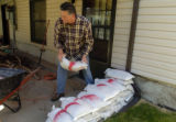 Larry Taylor (cq) loads sandbags into a wheelbarrow Tuesday morning May 24, 2005 at his mothers...