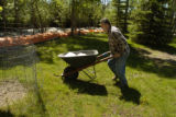 Larry Taylor (cq ) pushes a wheelbarrow full of sandbags Tuesday morning May 24, 2005 at his...