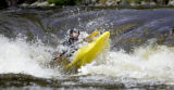Ian Schwendy (cq), 30, of Boulder, Colo., rides out of a chute in his kayak on Boulder Creek on...