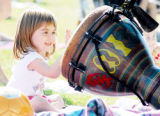 Aly Smerker, 3, of Littleton bangs on a djembe while in the crowd at the Istari African drumming...