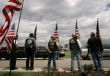 (PG8587) Bikers hold flags and line the road of the cemetary after the burial of Sgt. Isaac...