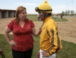 Trainer Elizabeth Brand (cq), left, talks to jockey, Adrian Romos, in the paddock, before his ride...