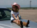 Hadley Petterson sits on a car in the parking lot, waiting with family for races to begin, Friday...