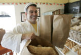 Greg Allan (cq) carries bags of bread at his store, Vincenza's Italian Bakery & Deli, in...