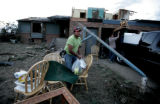 Jose Brito, loads as many family possession into a pick-up after his home was destroyed by a...