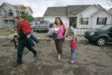 BG0071 A Colorado Highway Patrolman helps evacuate a mother and her childeren (((NO NAMES))))) in...