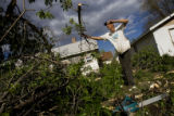DM0452  Working with the company Waste Chasers Terry Bird cleans up a tree damaged from the...