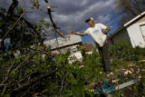 DM0454  Working with the company Waste Chasers Terry Bird cleans up a tree damaged from the...