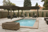 The backyard, landscaped with concrete pavers and a small swimming pool that the owners use...