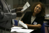 MJM172  Martha Calderon (cq) watches as Jerome Cooper holds up a sample voting ballot during a...