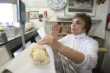 Rose Carbone wraps a sausage sandwich behind the counter at Carbone's Sausage Market and Deli on...