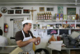 Nick Lonardo weighs some sausage for a customer at the counter Carbone's Sausage Market and Deli...