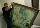 Parsons employee Luis Aguilera moves a relief map depicting the Dams Project, which was an...