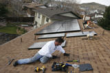 DM0095  Randy Gonser with Akeena Solar installs solar panels on the roof of a home in Lakewood,...