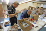 L to R: Volunteers Chris Michalik (cq) and Bill Scharfenberg (cq)  sort out canned goods and rice...