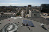 Workers from Bella Energy install solar panels on the roof of Colorado's state capitol building...