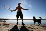 Christopher Peters gets ready to hit a ball into the water for his dog, Bear Bear, to retrieve,...