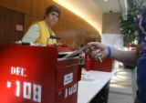 Poll worker, Kathleen Martinez (cq) keeps an eye on the drop off box, Monday morning, November, 3,...
