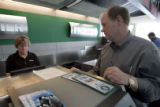 Air passengers David Smith, of Kansas City, right, gets help changing seats from Frontier Airlines...