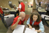 Temporary election workers Richard Bettinger, left, and Sally Hobson, read a ballot that didn't...