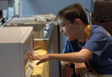 Eric Stahlman, 12, of Littleton, Colorado checks out a talking microwave at The Collaborative...