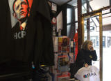 (017) Laura Vance, 60, of Denver, consults a friend by phone while she shops for Obama t-shirts ...