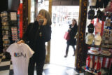 (018) Laura Vance, 60, of Denver, consults a friend by phone while she shops for Obama t-shirts ...