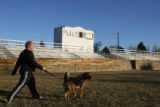 Pete Megyesy (cq) walks his dog, Andre, on the football field at Harvard Gulch Park, 660 E. Iliff,...