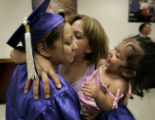 Yuri Frias, 18, a single mother, of Denver, left, gets a hug from her mother, Norma Frias, center,...