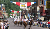 Ryan Soderlin/Journal staff Riders carry flags as they make their way through downtown Deadwood...
