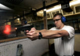 Recruit Officer Dan Politica (cq), 23, of Arvada, fires his weapon during firerarms training at...