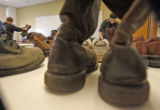 (at right) Navy veteran Gabriel Douglas (cq) sorts through the used shoes offered at one of the...