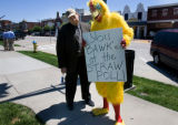 M.E. Sprengelmeyer poses with a costumed chicken that protested outside a John McCain event in...