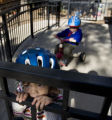 (170) Season to Share: Joselyn Do, 2, of Boulder, pauses her tricycle ride to peek through a...