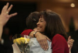 Highlands Ranch High School teacher, Susan Elliott, right, gets a hug from one of her students,...
