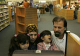 Soud Al Taai, Jaafar Al Saad (far right),  and their daughters Zainab, 6, and Nour, 4,  play...