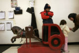 Soud Al Taai, right, gives her daughter Nour, 3, a penny for the horse ride in King Soopers while...