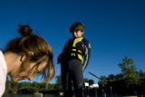 Alex Whitney, 10 (cq) stretches on the dock before heading out to skateboard on Pit 4 lake near...