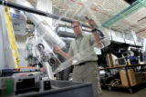 Matt Keyser (cq), senior engineer at the Energy Storage Lab, lifts a casing off a nickel metal...
