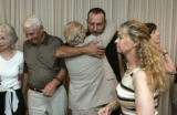 Attorney Jeff Anderson (cq), center, hugs Randy Becker after he announced a settlement for 12...