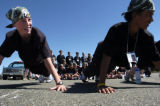 Group leader Peter McLeod (cq), left, and Derrick Whitfield (cq), right, do pushups during the...