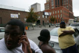 Jason Jackson, 28, (cq) (white shirt) leans against his car talking on  the phone as J.P., 28,...