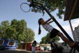 MJM724  Litzy Lastra (cq), 7, climbs on a basketball hoop outside her family's mobile home Friday...